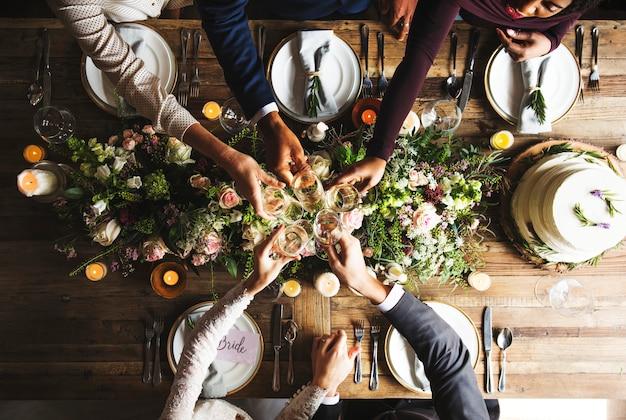 Mensen cling wijnglazen op huwelijksreceptie met bruid en bruidegom