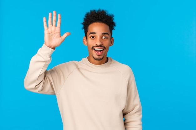 Mensen, communicatie en chatten concept. de gelukkige uitgaande glimlachende aardige afrikaanse amerikaanse kerel met snor en afrokapsel die nieuwe vrienden ontmoeten, hallo golf zeggen dient hallogebaar in, blauw