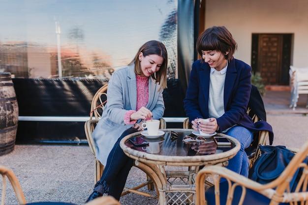 Mensen, communicatie en vriendschapsconcept - glimlachende jonge vrouwen die koffie of thee drinken en bij openluchtterraskoffie spreken