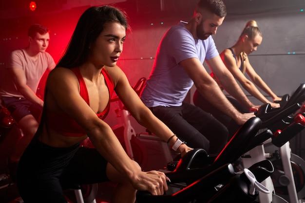 Mensen concentreerden zich op het afvallen met machine-aerobics voor een slank lichaam, zittend op de fiets, intensieve cardiotraining in de fitnessruimte