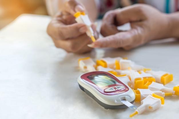Mensen controleren de bloedsuikerspiegel met glucometer thuis en accessoires