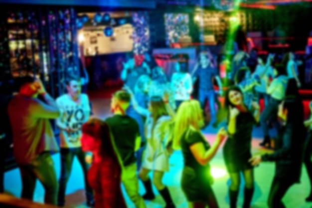Mensen dansen op de dansvloer in een nachtclub, veel mensen. heldere stroboscooplampen. er is geen focus, onscherpe achtergrond