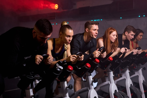 Mensen die afvallen met machine-aerobics voor een slank lichaam, zittend op de fiets, intensieve cardiotraining in de fitnessruimte