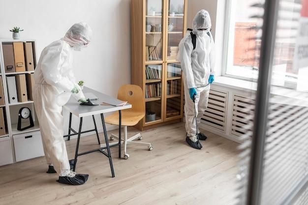 Mensen die beschermende uitrusting dragen om een gevaarlijk gebied te desinfecteren