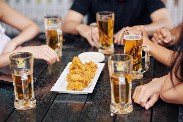 Mensen die bier met kip drinken