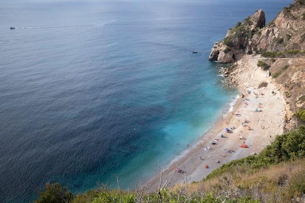 Mensen die bij mooi weer genieten van een mediterraan strand omringd door kliffen
