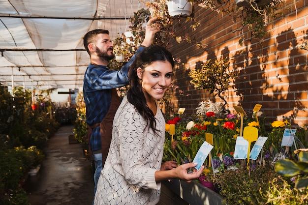 Mensen die bloemen in serre behandelen