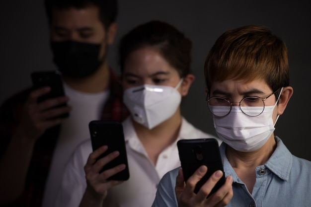 Mensen die chirurgische maskers dragen en hun telefoon gebruiken, kijken bezorgd en bezorgd over de pandemie-uitbraak en nieuws van sociale media