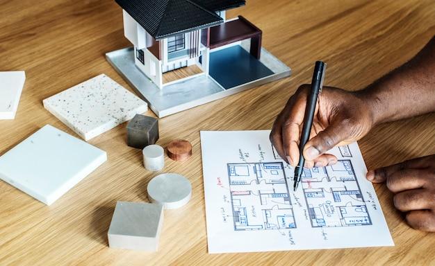 Mensen die de blauwdruk van het huisplan schetsen