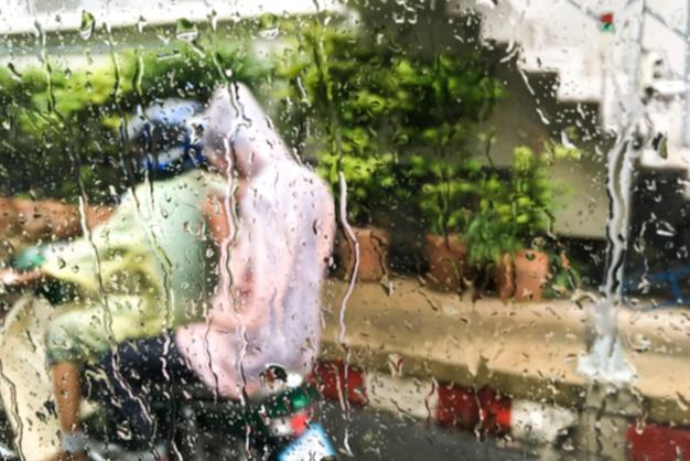 Mensen die de kleren dragen die van de regekleur een motorachtergrond berijden regenachtige dag.