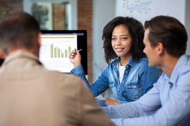 Mensen die een digitaal apparaat gebruiken tijdens een vergadering