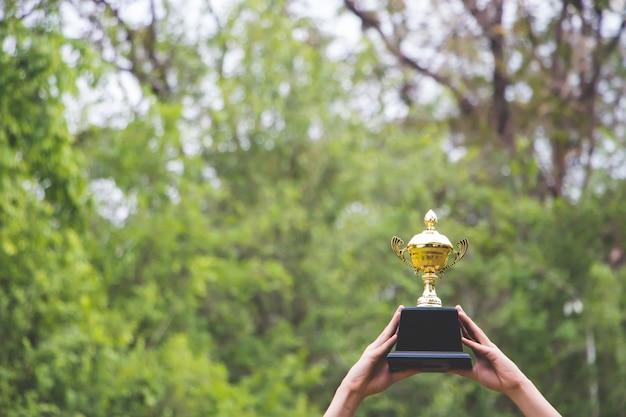 Mensen die een gouden trofee boven hun hoofd heffen, hebben een groene boomachtergrond.