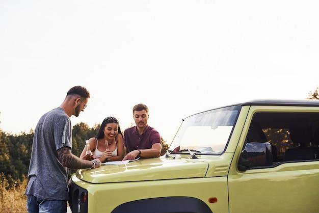 Mensen die een kaart lezen die op de motorkap van de auto ligt