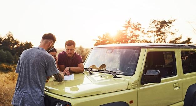 Mensen die een kaart lezen die op de motorkap van de auto ligt Premium Foto
