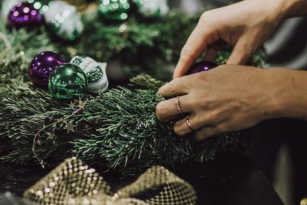 Mensen die een kerstkrans maken met kerstversiering
