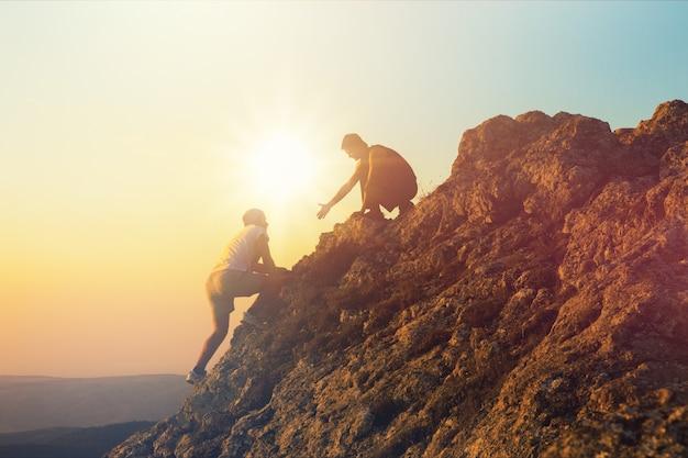 Mensen die elkaar helpen naar boven te wandelen