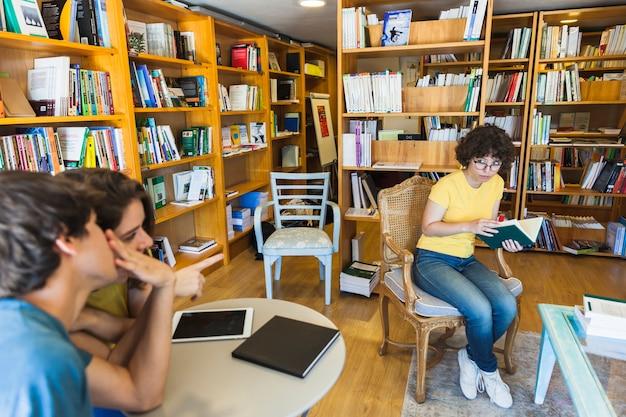Mensen die geeky vrouw in bibliotheek bespreken