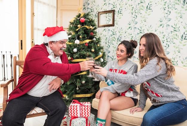 Mensen die glazen dichtslaan dichtbij groene kerstboom