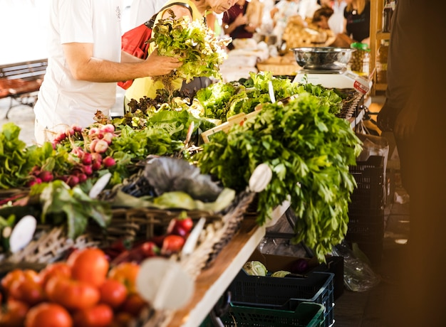 Mensen die groente van lokale plantaardige markt kopen
