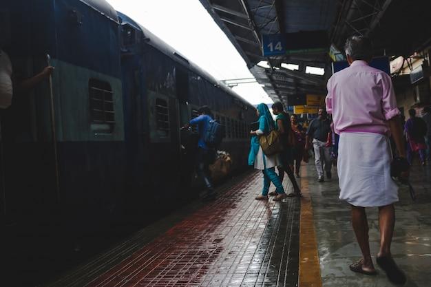 Mensen die haasten om een trein aan boord te gaan als een man in een roze shirt lopen langs