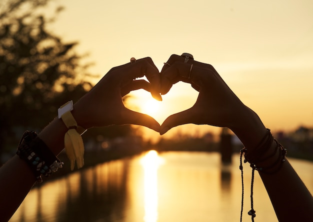 Mensen die handen in hartvorm maken silhouetzonsondergang