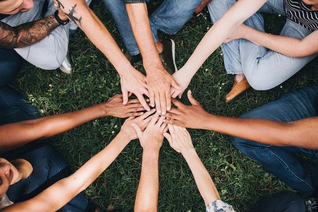 Mensen die handen samen in het park stapelen