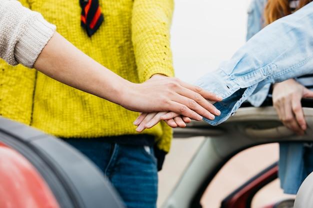Mensen die handen samenbrengen dichtbij auto