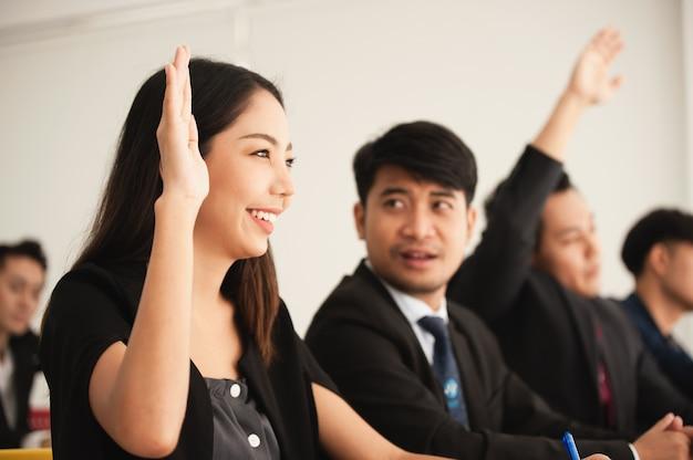 Mensen die hun hand opsteken om vragen te stellen tijdens de vergadering