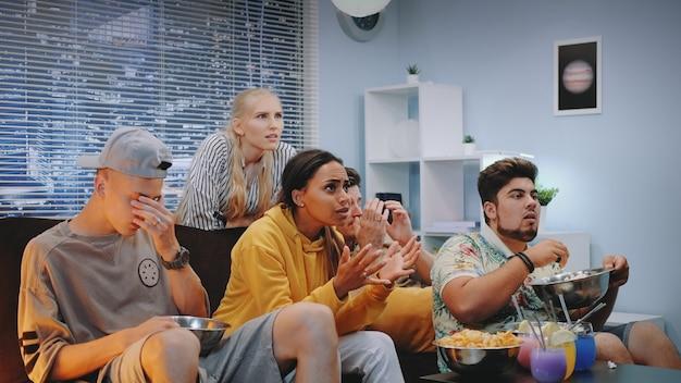 Mensen die hun negatieve reactie op actie op tv laten zien.