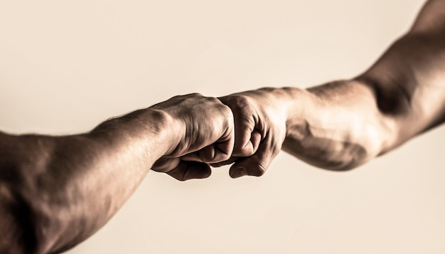 Mensen die hun vuisten tegen elkaar stoten, armen. vriendelijke handdruk, groeten van vrienden. man die vuist hobbel geeft. handen van man mensen vuist hobbel team teamwerk, succes.