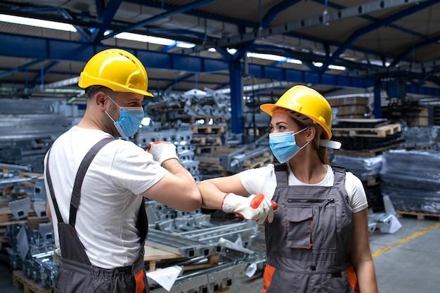 Mensen die in de fabriek werken, raken met ellebogen en groeten vanwege coronavirus en infectie