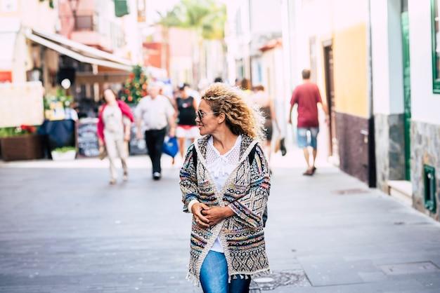 Mensen die in de stad lopen en een toeristische conceptlevensstijl met een vrolijke en trendy volwassen vrouw die alleen van de stad geniet en van de winkeltijd geniet