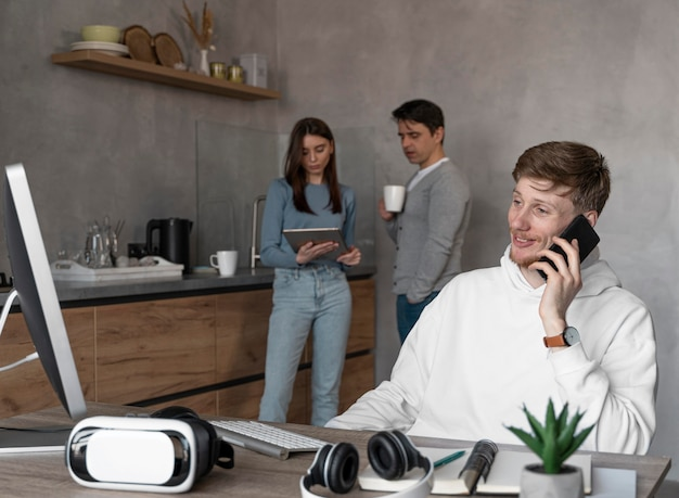 Mensen die in het mediagebied met computer werken en aan de telefoon praten