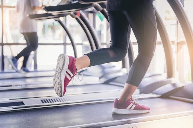 Mensen die in machinetreadmill bij fitness gymnastiek lopen