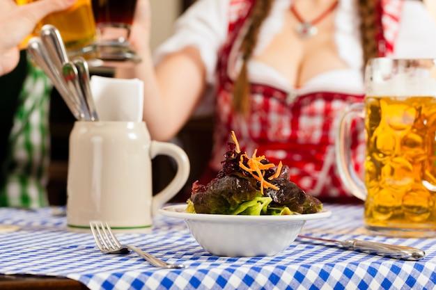 Mensen die in traditionele beierse tracht in restaurant of bar eten