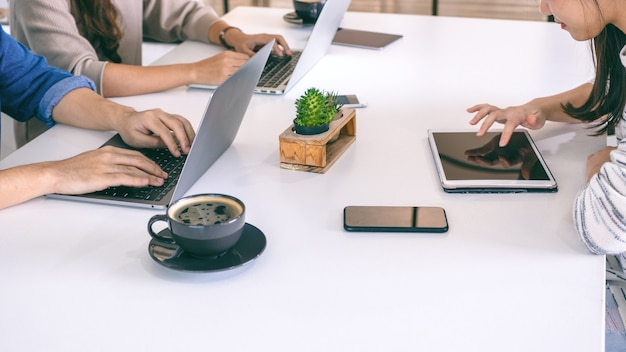 Mensen die laptopcomputer en tablet-pc gebruiken en werken met mobiele telefoon op tafel op kantoor
