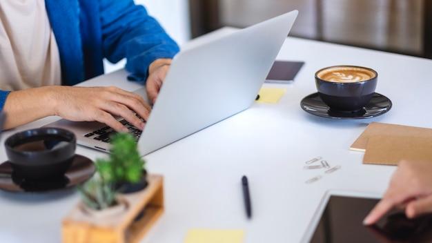 Mensen die laptopcomputer en tablet-pc gebruiken en werken op de tafel op kantoor