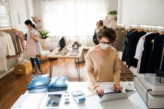 Mensen die masker dragen in kledingwinkel die in het nieuwe normaal winkelen