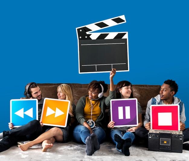 Mensen die media spelerpictogrammen en een kleppictogram houden