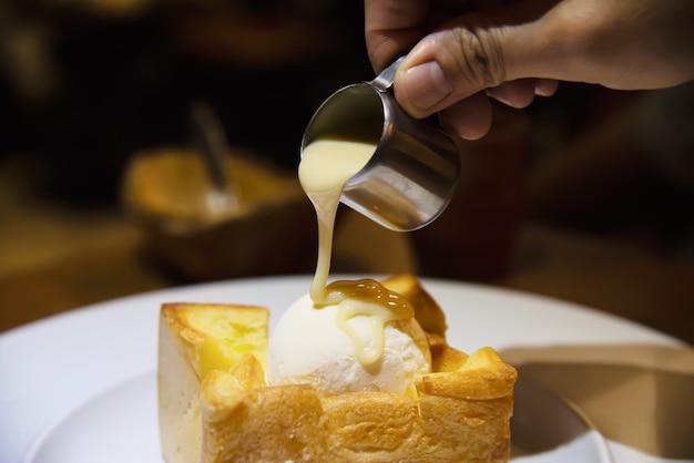 Mensen die melk op de toost van het roomijsbrood gieten