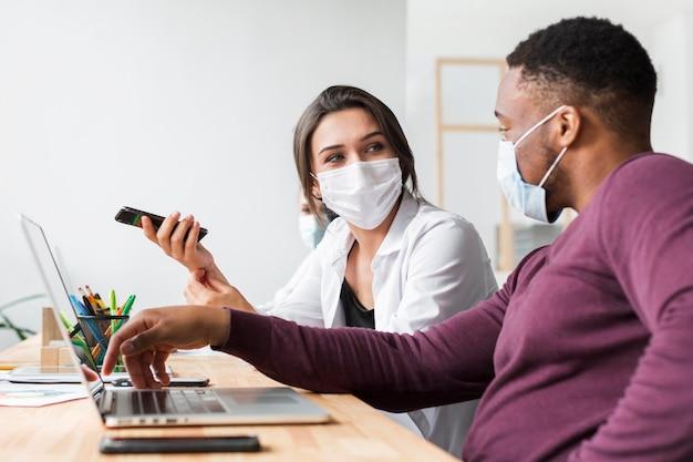 Mensen die met maskers op kantoor communiceren tijdens pandemie