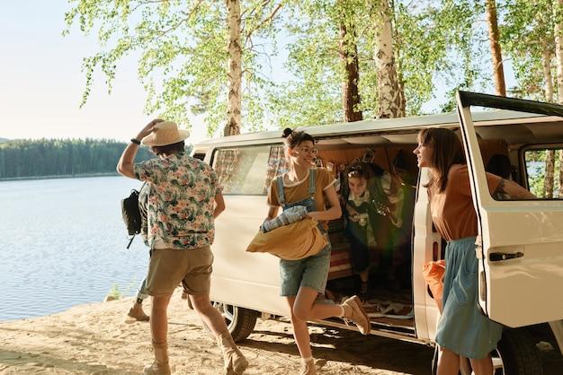 Mensen die met tassen uit het busje stappen en de camping in het bos regelen