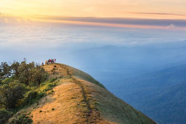 Mensen die naar bovenkant van berg met ochtendzonsopgang wandelen