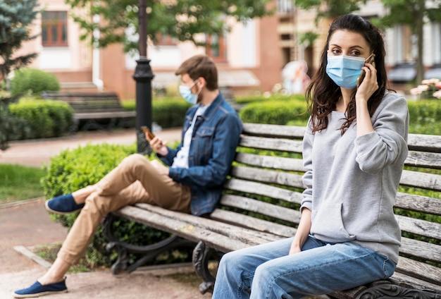 Mensen die op een bankje de sociale afstand respecteren
