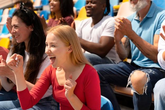 Mensen die op een zonnige dag naar een voetbalwedstrijd kijken