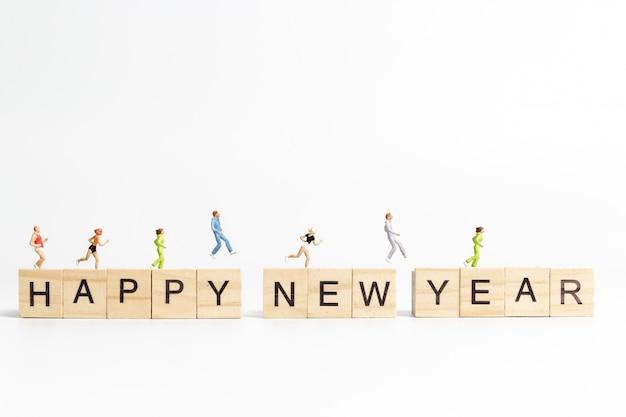 Mensen die op happy new year belettering houten blok lopen