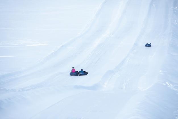 Mensen die op snowtubing rijden in de kopieerruimte van het winterpark