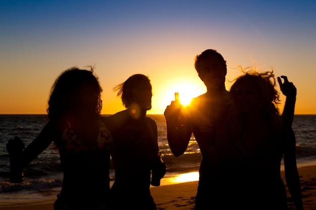 Mensen die partij hebben op strand met drankjes