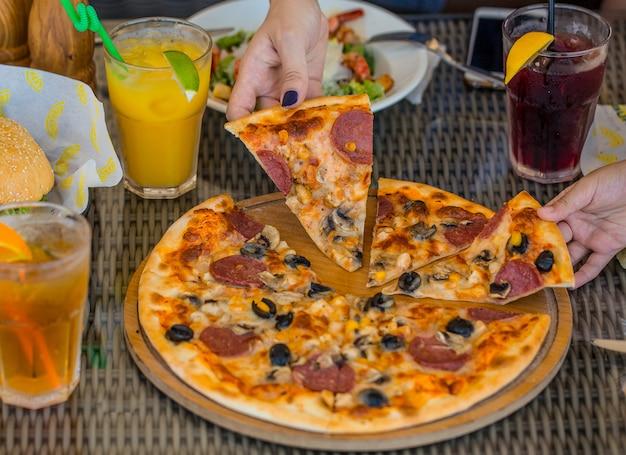 Mensen die plakjes pizza met olijfpeperoni nemen