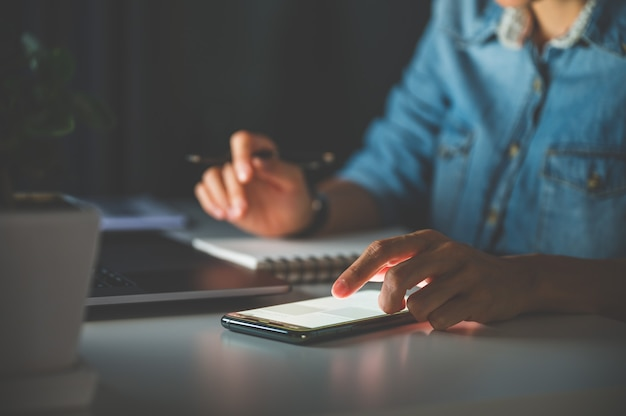 Mensen die 's nachts op kantoor werken met behulp van laptop, mobiele telefoon, notebook of computer. zakelijk of werk vanuit huis concept.